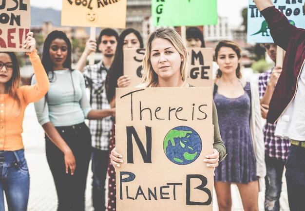 Группа демонстрантов на дороге, молодые люди из разных культур и рас борются за изменение климата