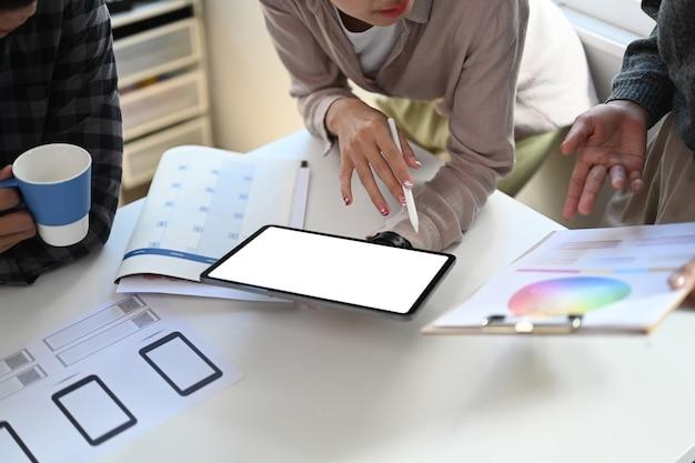 カジュアルな服装のデザイナーのグループが、会議用テーブルでデジタルタブレットとカラーキャリブレーションを使用しています。