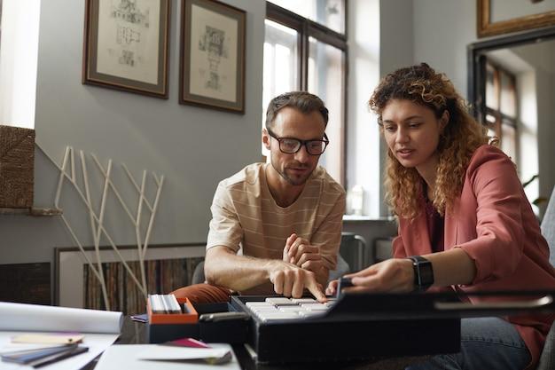 패턴을 검사하고 현대 사무실에서 팀에서 프로젝트를 논의하는 테이블에 앉아 디자이너 그룹