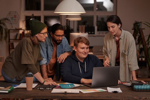 사무실에서 팀에서 온라인 프레젠테이션을 만드는 테이블에서 함께 노트북을 사용하는 디자이너 그룹