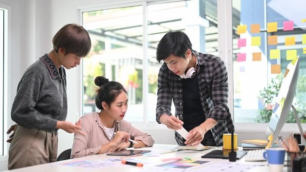 Группа дизайнеров вместе работает над проектом и делится идеями в творческом офисе.