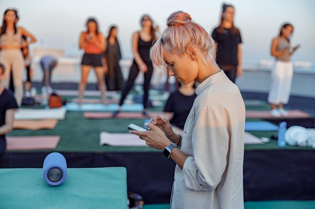 다른 사람들의 그룹은 여름 저녁에 아름다운 일몰에 옥상에서 명상 요가 연습을하고 있습니다