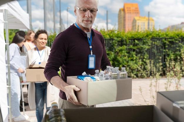 貧しい人々のためのフードバンクでボランティアをしているさまざまな人々のグループ