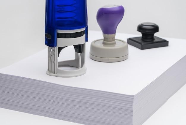 Группа различных штампов на пачке листов чистой бумаги