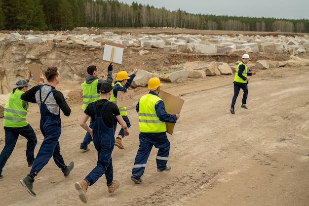 Группа недовольных строителей с плакатами, бегущими за подрядчиком вдоль строительной площадки