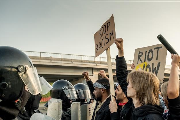 진압 경찰 앞에 서서 야외에서 모든 민족의 자유를 위해 싸우는 표지판을 들고 불쾌한 인종 간 사람들의 그룹