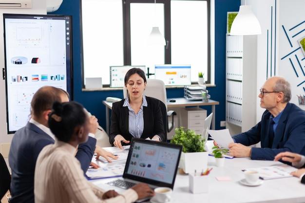 会議室で会議を行う多様なビジネスマンのグループ。新しいスタートアップ企業の財務戦略について同僚とアイデアを話し合う実業家。