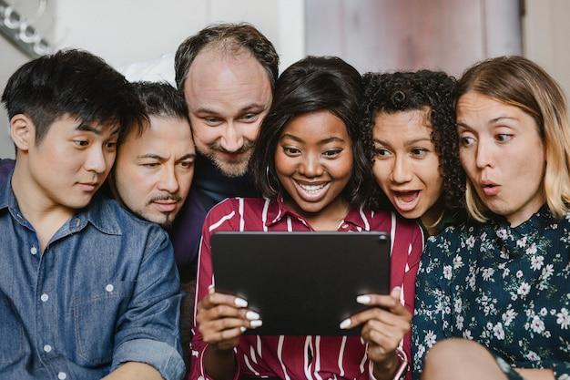 一緒にデジタルタブレットでコンテンツを見ている多様なビジネスマンのグループ