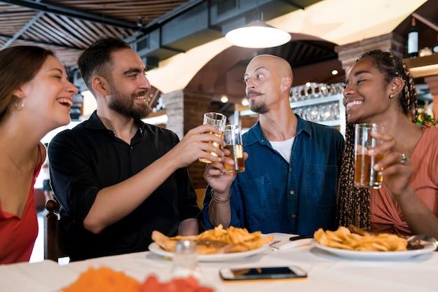 다양한 친구들이 레스토랑에서 함께 식사를 즐기면서 맥주 잔을 부딪히고 있습니다. 친구 개념입니다.