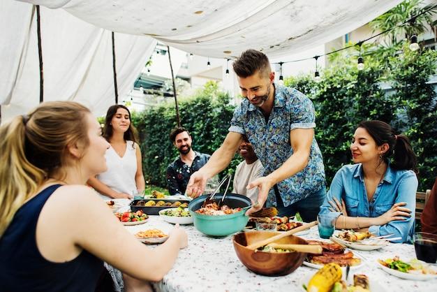 Группа разнообразных друзей, наслаждаясь летнюю вечеринку вместе