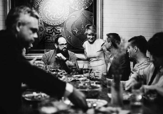 一緒に夕食を食べる多様な友人のグループ