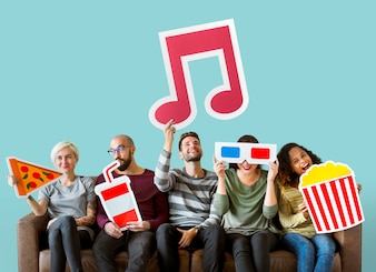 Group of diverse friends holding movie emoticons