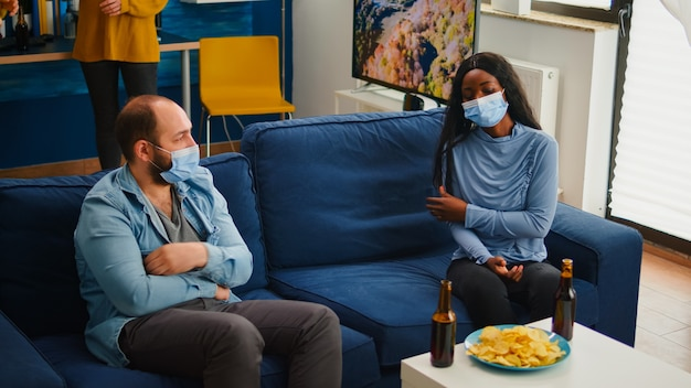 世界的大流行の際に祝う自宅の居間で、社会的距離を保ちながらマスクを着用して集まる多様な友人のグループ。多民族の人々が保護マスクを脱いでおやつを食べる