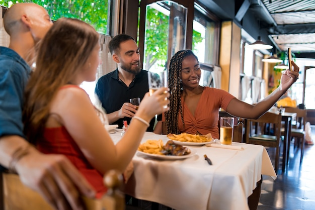 바에서 맥주 한 잔을 마시며 휴대폰으로 셀카를 찍는 다양한 친구들. 친구 개념입니다.