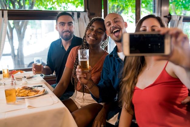 レストランで一緒に食事を楽しみながら携帯電話で自分撮りをしている多様な友人のグループ。友達のコンセプト。