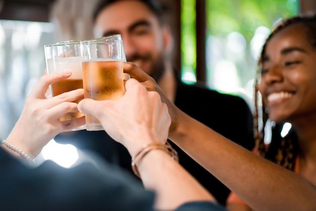 바 또는 펍에서 함께 시간을 즐기면서 맥주 잔을 들고 건배하는 다양한 친구들. 친구 개념입니다.