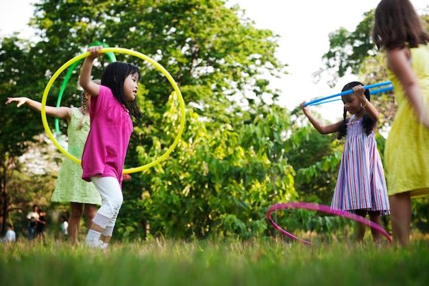 Группа разнообразных детей, играющих в обруч в парке вместе