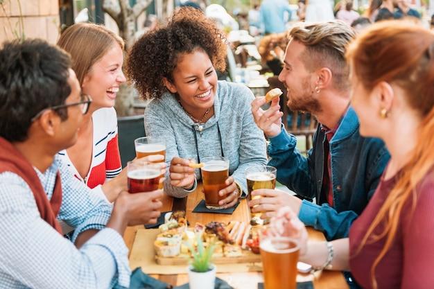 다양한 다민족 친구들이 술집에서 재미있는 시간을 보내고 뒤쪽에 있는 매력적인 젊은 흑인 여성에게 초점을 맞춰 시원한 맥주를 마시며 웃고 농담을 합니다.