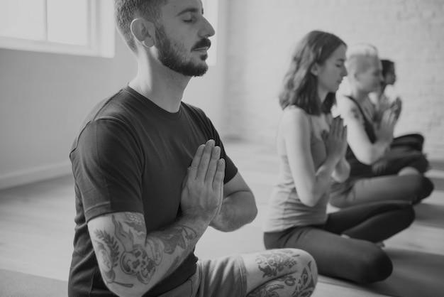 Группа разных людей присоединяется к классу йоги