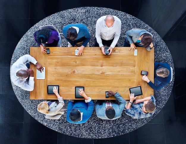 Группа разнообразных людей в таблице с использованием устройств