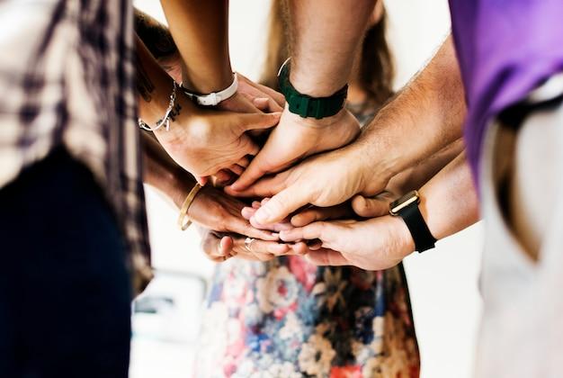 多様な人々のグループが手を組んでチームワーク