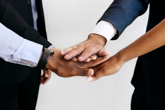 Группа разных людей, складывающих руки посередине