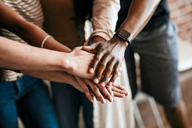 真ん中に手を積み重ねる多様な人々のグループ