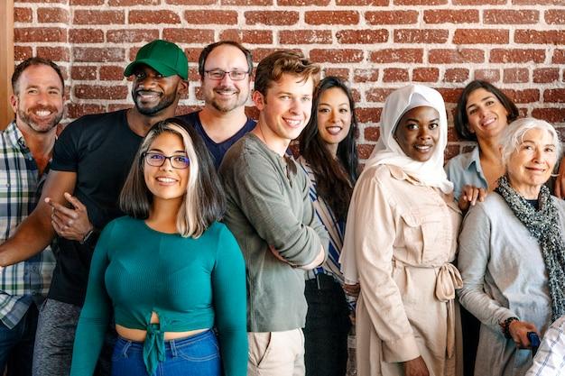 Группа разнообразных людей, стоящих перед кирпичной стеной