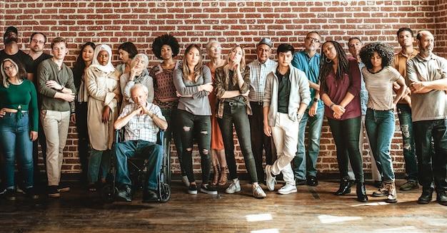 Группа разных людей, стоящих перед кирпичной стеной