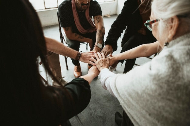 真ん中で手を組む多様なチームのグループ