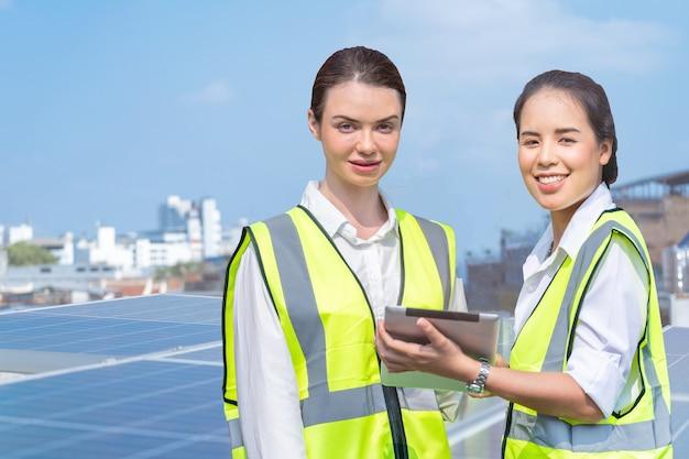 태양 전지 패널 옥상에서 검사하기 위해 회의를 하는 다양성 공장 노동자 여성 그룹