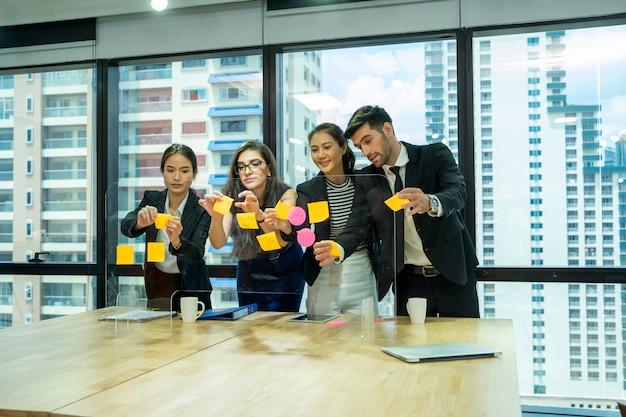 情報を検索する多様性の人々のグループは、新しいスタートアッププロジェクトでアイデアを提供し、粘着性のあるカラフルな紙でガラスの壁の後ろに立っています。ステッカーから単語を学ぶ陽気な学生