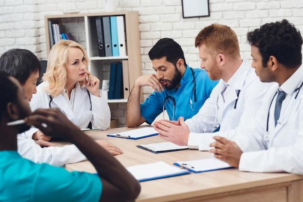 Группа врачей разных рас встречается за столом.