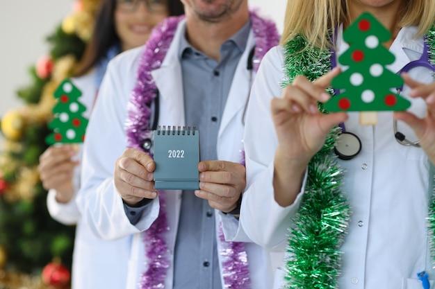 2022년 달력을 들고 진료소에서 크리스마스 트리를 들고 있는 의사 그룹