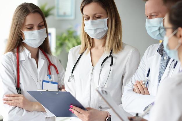 診療所で文書とクリップボードを持って立っている医療用保護マスクの医師のグループ