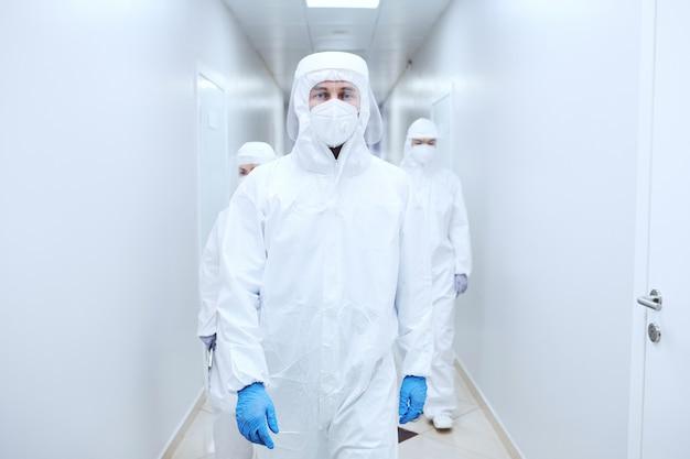 전염병 동안 병원 복도를 걷고 있는 보호복을 입은 의사 그룹