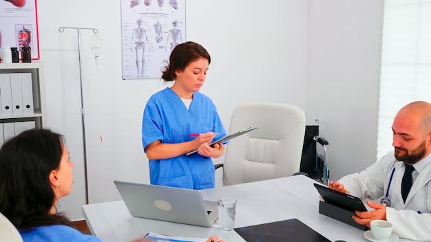 환자의 진단을 분석하는 유니폼을 입고 의료 사무실에서 함께 일하는 책상에 앉아 있는 의사 그룹. 질병에 대해 동료와 이야기하는 클리닉 전문 치료사, 의학 전문가