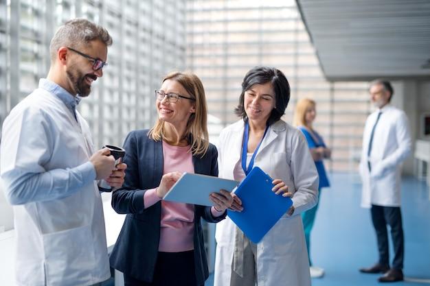 会議で医薬情報担当者と話している医師のグループ。
