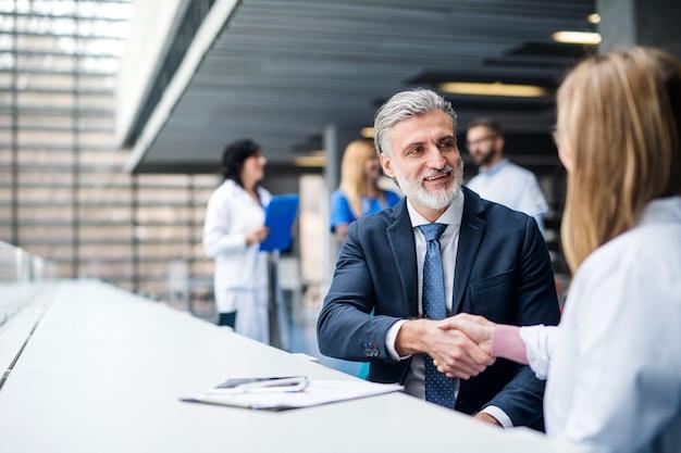 握手しながら医薬情報担当者と話している医師のグループ。