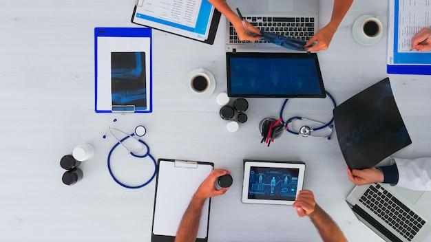 의사의 그룹이 함께 일하고, 메모를하고, 의료 회의를 갖는 모든 주위에 청진기와 디지털 장치로 책상에 앉아 상위 뷰 복사 공간에서 엑스레이를 분석