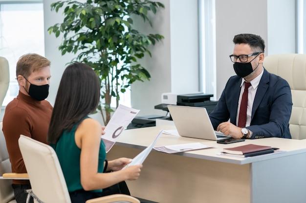 토론을 하는 보호 마스크를 쓴 경제학자 그룹