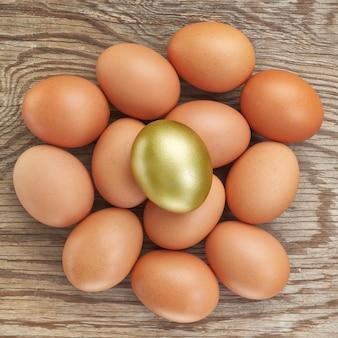 Группа яиц и один золотой. в пасху. на деревянной текстуре.