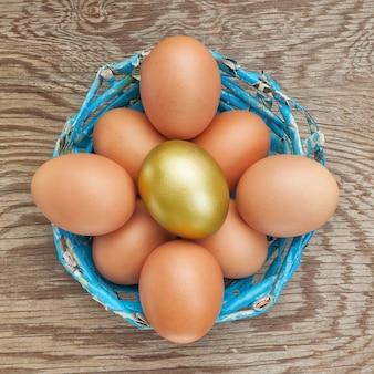 Группа в составе яйца в корзине голубом и золотом яичке. в пасху.