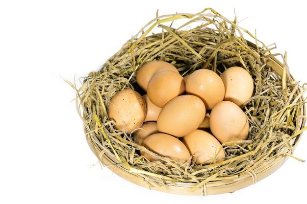 白で隔離された竹かごの中のわらの卵のグループ