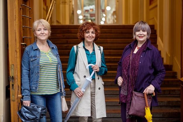 노인 여성 그룹은 백화점 입구에 서 있습니다.