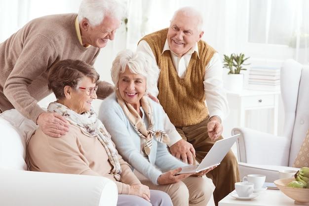 Группа пожилых людей, наслаждающихся современными технологиями в доме престарелых