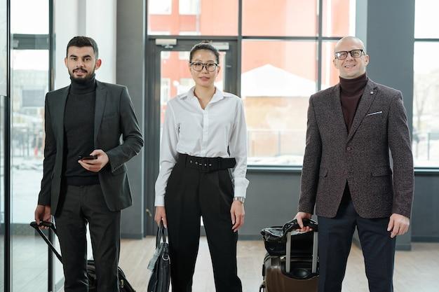 出発前に空港に立っているさまざまな民族や年齢のエレガントなビジネス旅行者のグループ