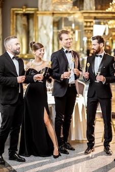 高級レストランホールでワイングラスを楽しみながら、年末年始を祝うレトロなスタイルに身を包んだエレガントな人々のグループ