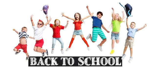 白いスタジオの壁に隔離されてジャンプするカラフルなカジュアルな服を着てジャンプする小学生や生徒のグループ