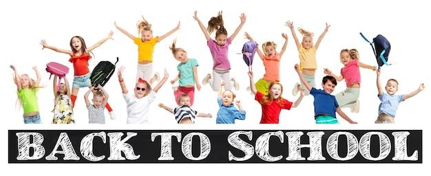 白でジャンプするカラフルなカジュアルな服でジャンプする小学生や生徒のグループ